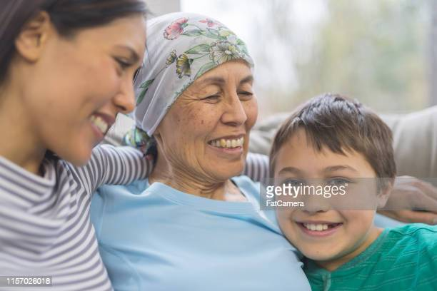 an ethnic woman in her 60s battling cancer sits cheerfully with her daughter and grandson on the couch - resilience stock photos and pictures