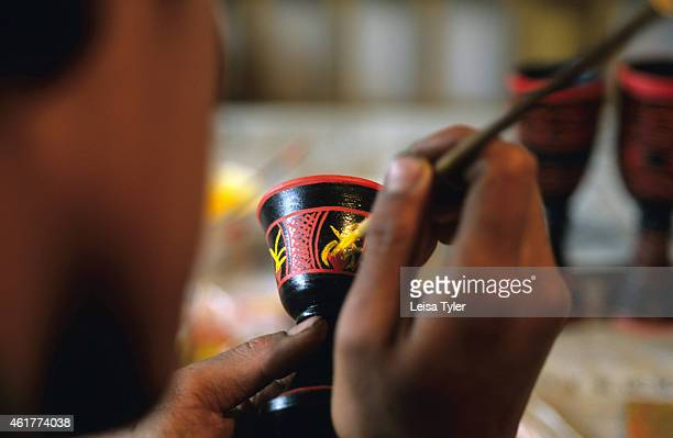 An ethnic Yi boy from Juilong village near Zhongdian starts to create a lacquered bowl. Lacquer, which is highly toxic in the raw form, is extracted...