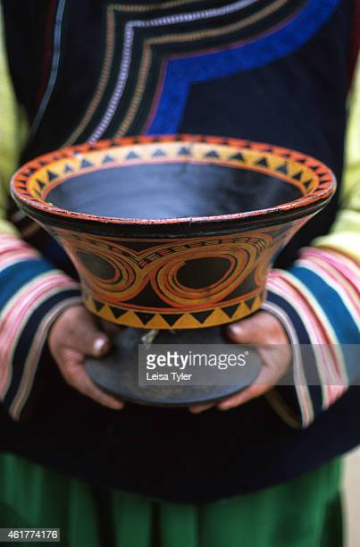 An ethnic Yi woman from Juilong village near Zhongdian holds a rare antique family heirloom- a lacquered bowl. Lacquer, which is highly toxic in the...