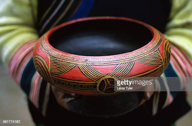An ethnic Yi woman from Juilong village near Zhongdian holds a rare antique family heirloom a lacquered bowl Lacquer which is highly toxic in the raw...