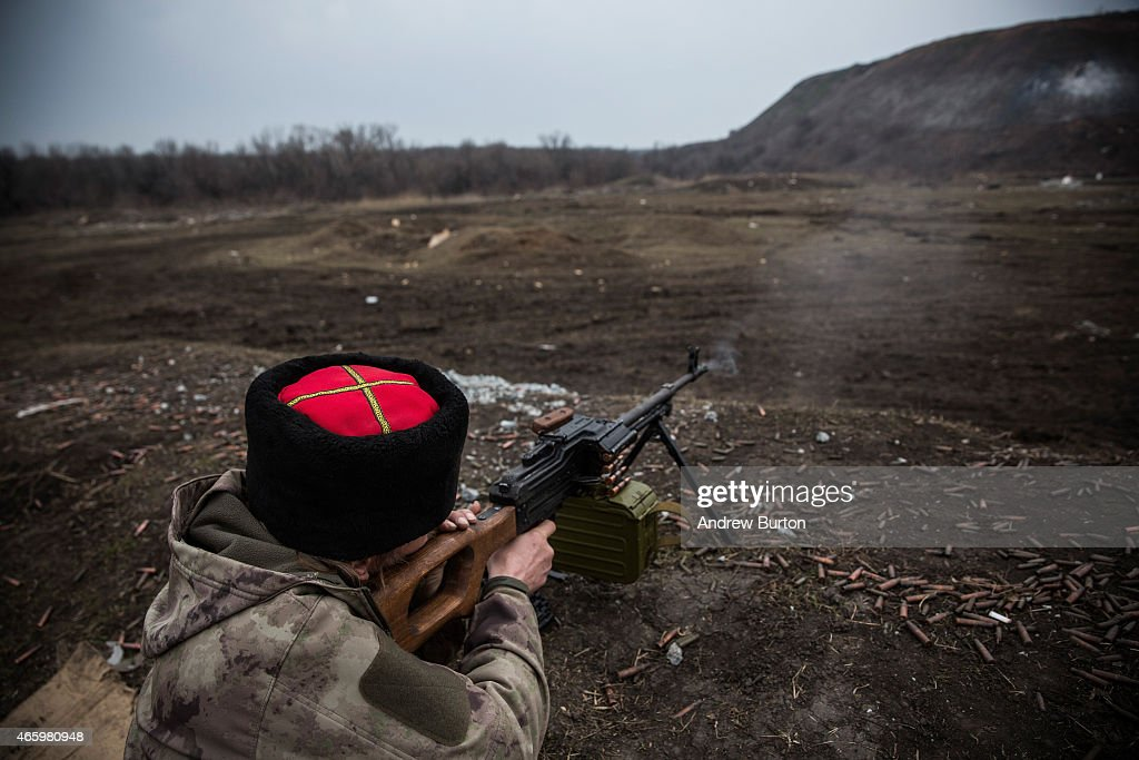 An ethnically Cossack pro-Russian rebel practices his firearms