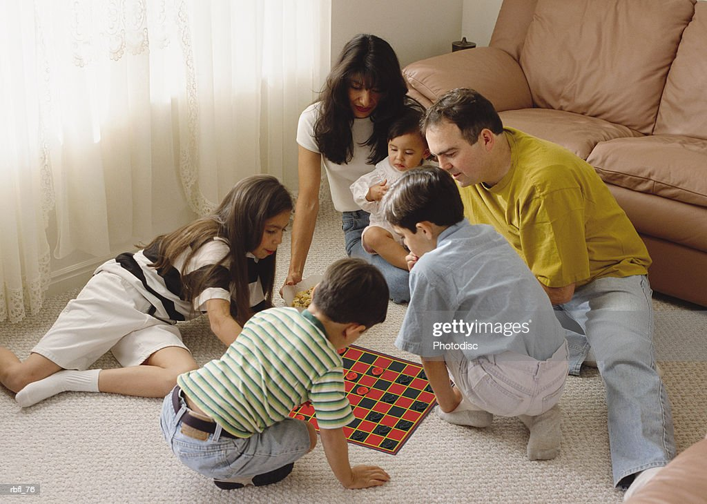 an ethnically mixed family sits in a circle playing a game : Stockfoto