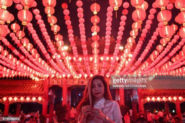 An EthnicChinese devotee burns josssticks and offers prayers at the Thean Hou temple decorated with red lanterns in Kuala Lumpur on February 15 2018...