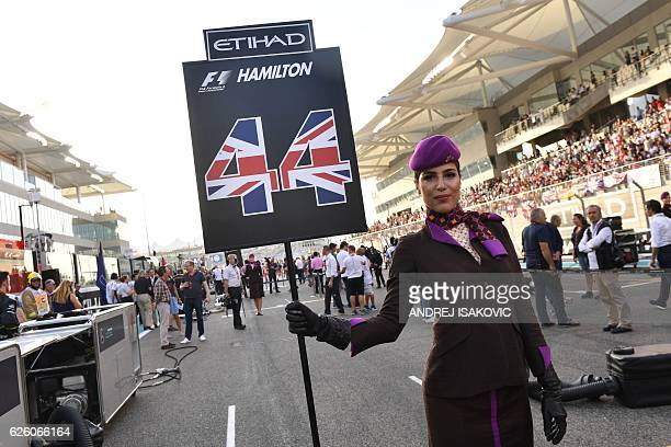 An Etihad Airways' cabin crew member holds a sign with the number Mercedes AMG Petronas F1 Team's British driver Lewis Hamilton ahead of the start of...