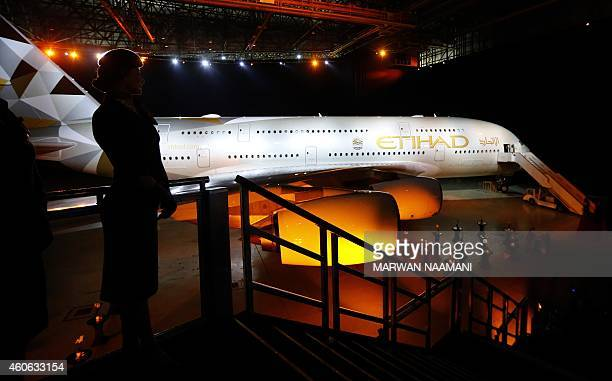 An Etihad airways flight attendant stands in front of the new Etihad A380 Airbus superjumbo at Abu Dhabi airport on December 18 2014 after the Abu...