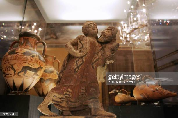 An Etruscan blackfigured amphora depicting the death of Medusa and of the Gorgon sister a Etruscan antefix portraying Sileno and Menade dancing and...
