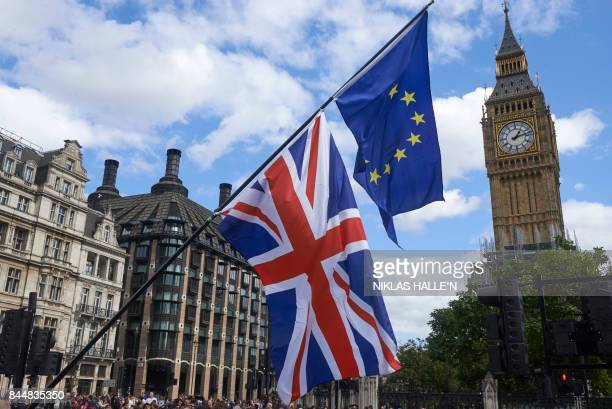 An EU and a Union Flag are seen in front of Elizabeth Tower during a proEU rally at the People's March for Europe against Brexit in Parliament Square...