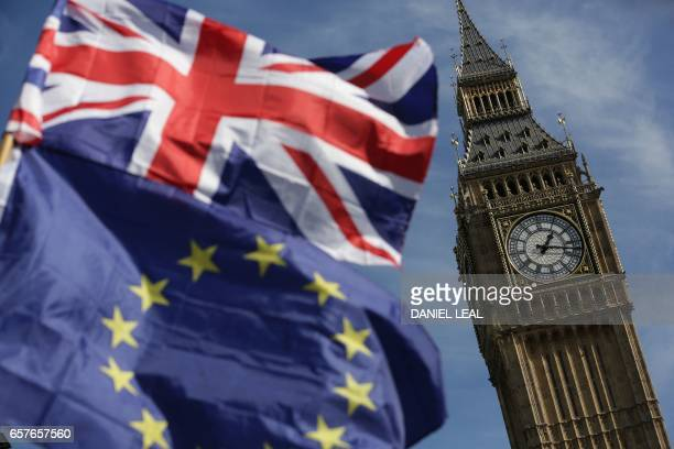 An EU flag and a Union flag held by a demonstrator is seen with Elizabeth Tower and the Houses of Parliament as marchers taking part in an...