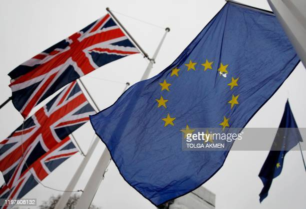 An EU Flag flown by an antiBrexit protester is seen with Union Flags set on a flag pole in Parliament sq1uare in front of the Houses of Parliament in...