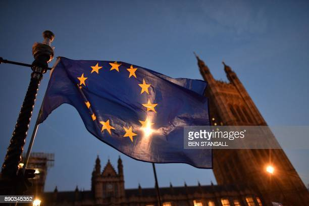 An EU flag is seen as proEU protesters demonstrate outside the Houses of Parliament in central London on December 11 2017 as Britain's Prime Minister...