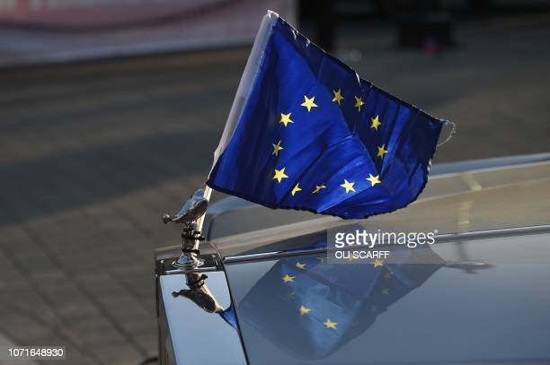 An EU Flag is seen displayed on the bonnet of a Rolls Royce car near the Houses of Parliament in central London on December 11 2018 British Prime...