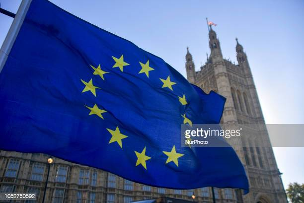 An EU flag waves outside the Parliament london on October 22 2018 Theresa May is to tell MPs the Brexit divorce agreement with Brussels is now 95%...