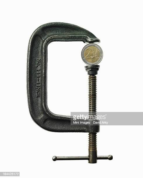 An European currency coin in a metal clamp. Euro.