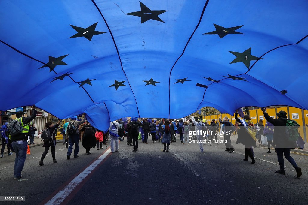 An European Union flag is held up as people take part in anti-Brexit and anti-austerity protests as the Conservative party annual conference gets underway at Manchester Central on October 1, 2017 in Manchester, England. Five-hundred thousand people are expected to take part in the protests with police mounting an unprecedented security operation of a thousand officers and extra armed police to protect Conservative party conference delegates.