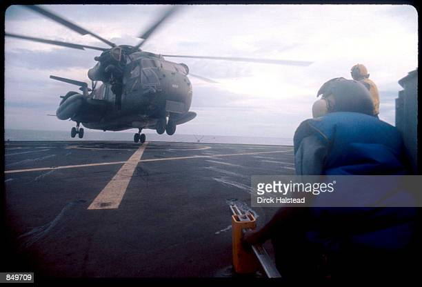 An evacuation helicopter lands onboard a US Navy ship April 30 1975 near Saigon Vietnam filled with civilians trying to flee the city after Saigon...