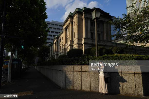 An evening commuter uses a smartphone outside the Bank of Japan headquarters in Tokyo, Japan, on Sept. 27, 2021. TheBank of Japan willrelease its...