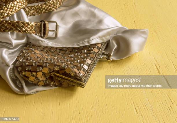 an evening golden purse and belt escaping from a silk sack - gold purse stock photos and pictures
