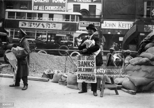 An Evening Standard newspaper vendor carrying a poster saying 'Hatry Crisis, Banks Dilemma', referring to financier Clarence Charles Hatry, a...