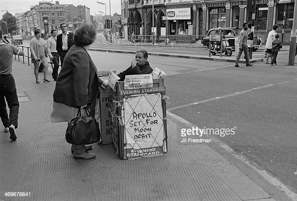 An Evening Standard sellers headlines cover the Apollo lunar orbit and a bus strike in London, City Road, central London, circa June 1969.