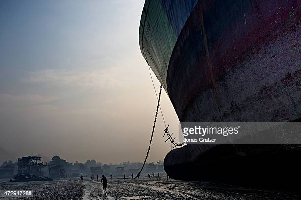 An evening sunset scene of a mega freighter that is out of service and has been left on Chittagong beach to be disassembled by poor laborers. Where...