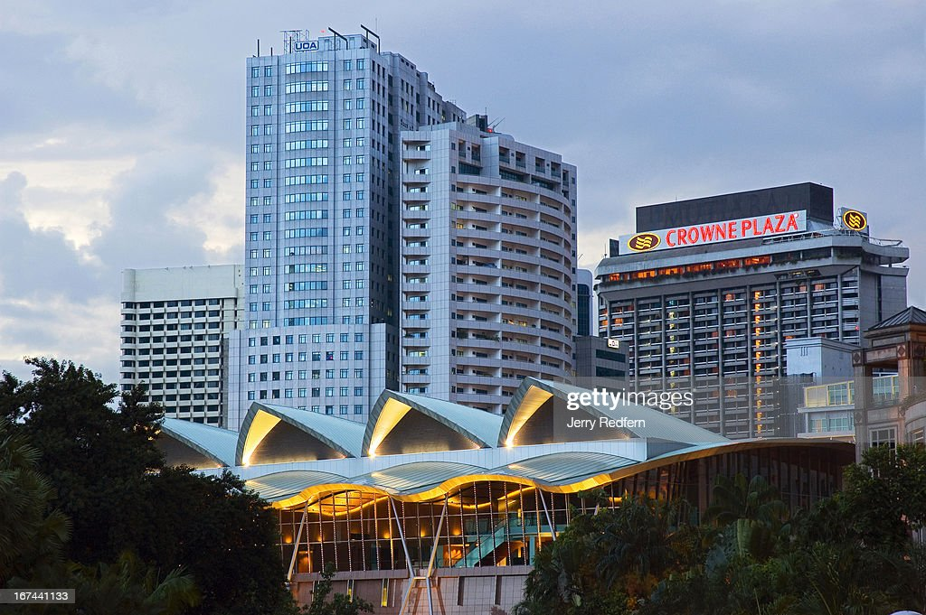 An evening view of buildings surrounding the KLCC gardens, including the KLCC Convention Centre, at the bottom, and the Crowne Plaza Hotel..