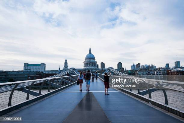 an evening view of millennium bridge with st. paul's cathedral in the background - ロンドン サウスバンク ストックフォトと画像
