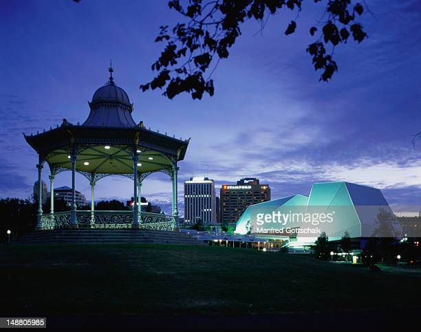 an evening view of the modern adelaide festival centre with the antique elder park rotunda in the foreground. - adelaide festival stock pictures, royalty-free photos & images
