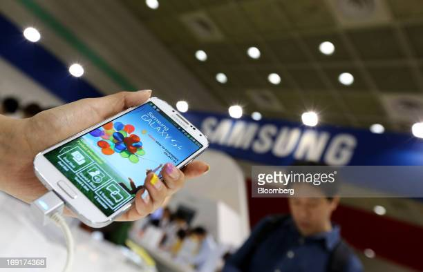 An event employee displays a Samsung Electronics Co. Galaxy S4 smartphone at the World IT Show 2013 in Seoul, South Korea, on Tuesday, May 21, 2013....