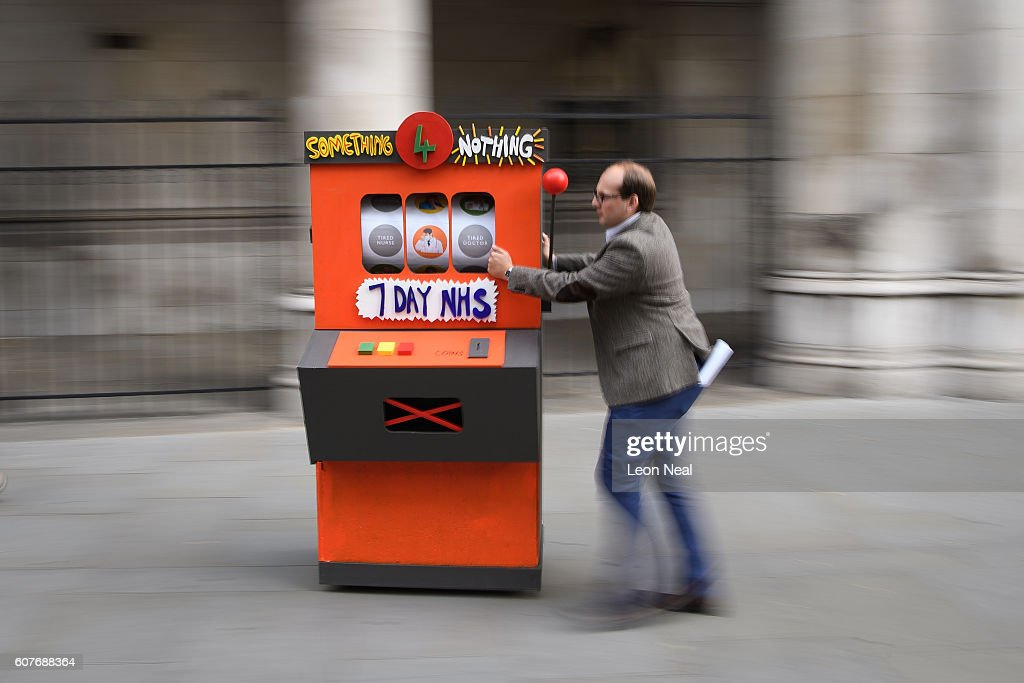 An event organiser removes a fake slot machine after junior doctors and supporters rallied outside the Royal Courts of Justice, Strand on the first day of their hearing as they challenge the government's plan for a seven-day NHS service, on September 19, 2016 in London, England. Justice for Health was founded in March 2015 by five frontline junior doctors to mount a legal challenge against the proposals by Jeremy Hunt, the Secretary of State for Health, to provide a full NHS service over the weekend, despite claims by opponents that the plan is under-funded and has not been fully considered.