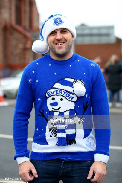 An Everton fan poses for a photo in a Christmas jumper outside the stadium prior to the Premier League match between Everton FC and Chelsea FC at...