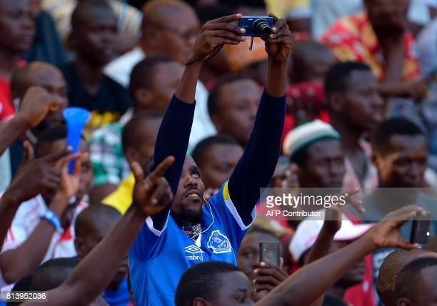 An Everton FC supporter takes a picture prior to a friendly football match between Everton and Kenya's Gor Mahia at the DaresSalaam stadium on July...