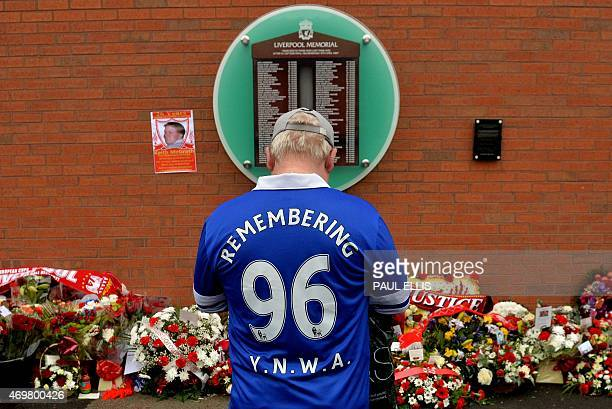 An Everton supporter stands in front of the temporary Hillsborough memorial ahead of a memorial service at Anfield in Liverpool north west Engand on...