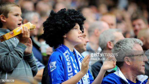 An Everton supporter wearing a wig similar to the hair of Everton's Belgian midfielder Marouane Fellaini applauds the team as they play against Wigan...