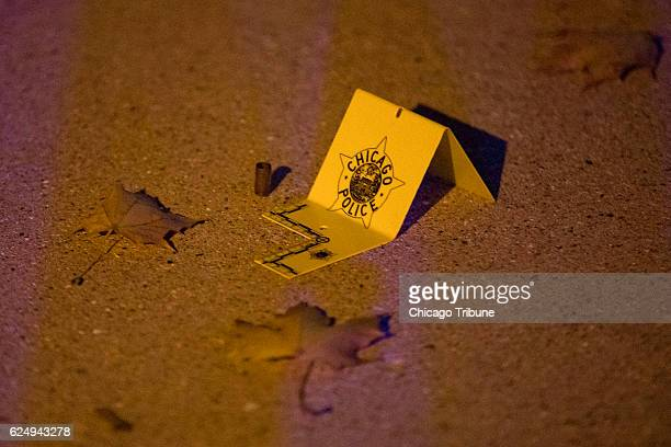 An evidence marker is placed next to a shell casing at the scene where four people were shot in the 5000 block of West Wabansia Avenue Friday Nov 18...