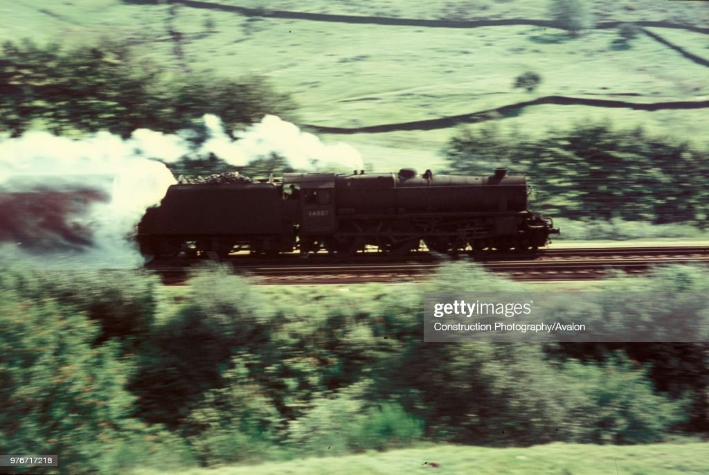 An ex LMS Black 5 picks up water at speed from troughs