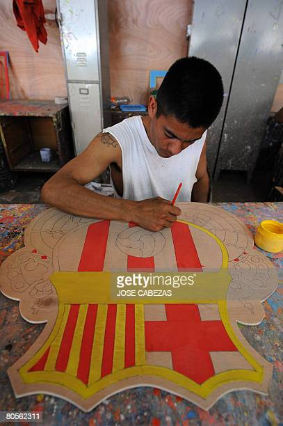 An ex member of the Mara Salvatrucha gang makes a crest of the Spanish football team Barcelona during a handicraft workshop on April 7 2008 as part...