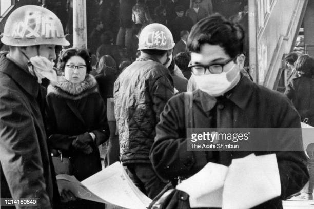 An exam takers wearing a mask walks past leftish students distributing flyers at the University of Tokyo on March 3, 1972 in Tokyo, Japan.