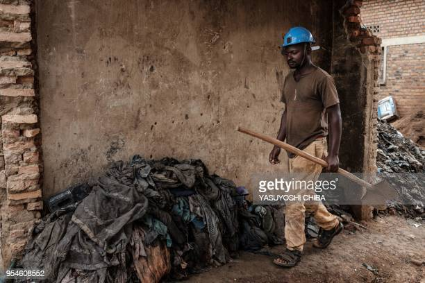 An excavation worker walks beside the victims' items after being collected from a pit which was used as a mass grave during 1994 Rwandan genocide at...