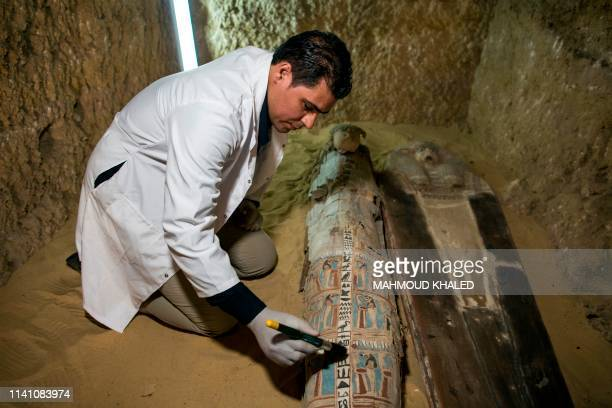 An excavation worker works inside a burial shaft at the Giza pyramid plateau on the southwestern outskirts of the Egyptian capital Cairo on May 4...