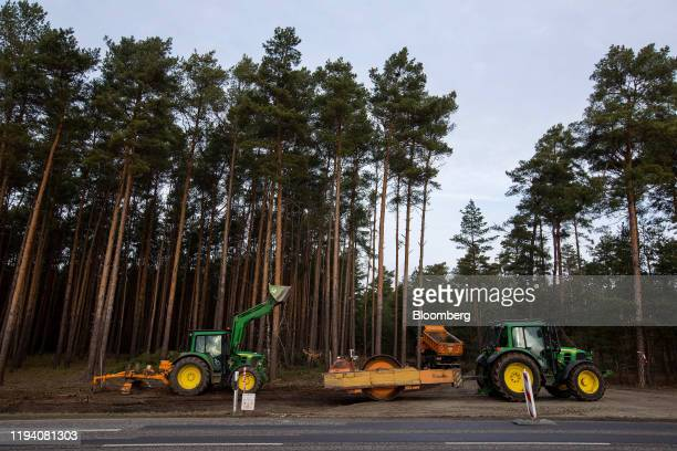 An excavator and a tractor drawn road roller sit beside a forest access road as a truck enters during groundworks for the Tesla Inc Gigafactory in...