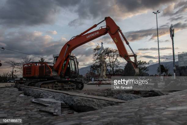 An excavator clean up the ruins after the tsunami and earthquake on October 8, 2018 in Palu, Central Sulawesi, Indonesia. The death toll from last...