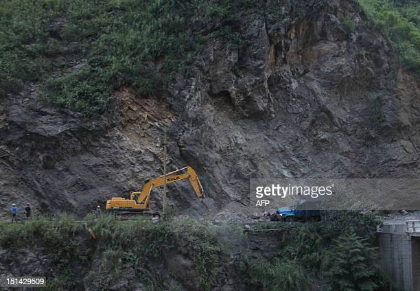 An excavator clears a road after a rock-fall in Yiliang, southwest China's Yunnan province on September 7 following two shallow quakes that struck...