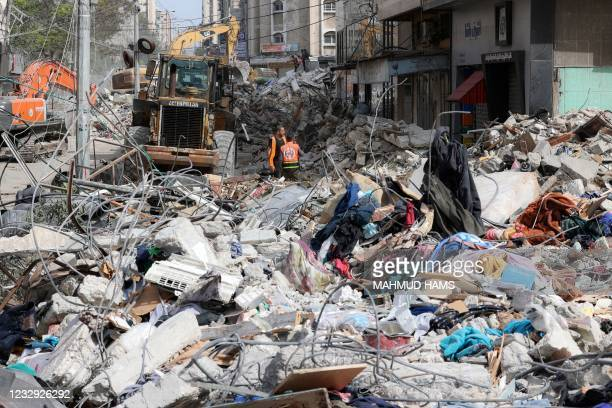 An excavator clears the rubble of a destroyed building in Gaza City's Rimal residential district on May 16 following massive Israeli bombardment on...