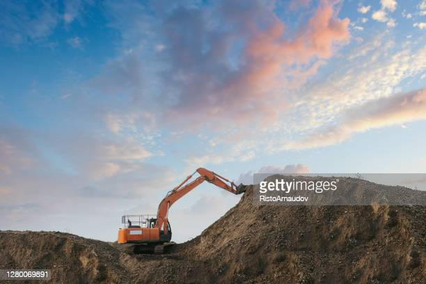 une excavatrice déterrant la saleté dans une fosse de sable - pelle photos et images de collection