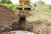 an excavator digs trench for laying