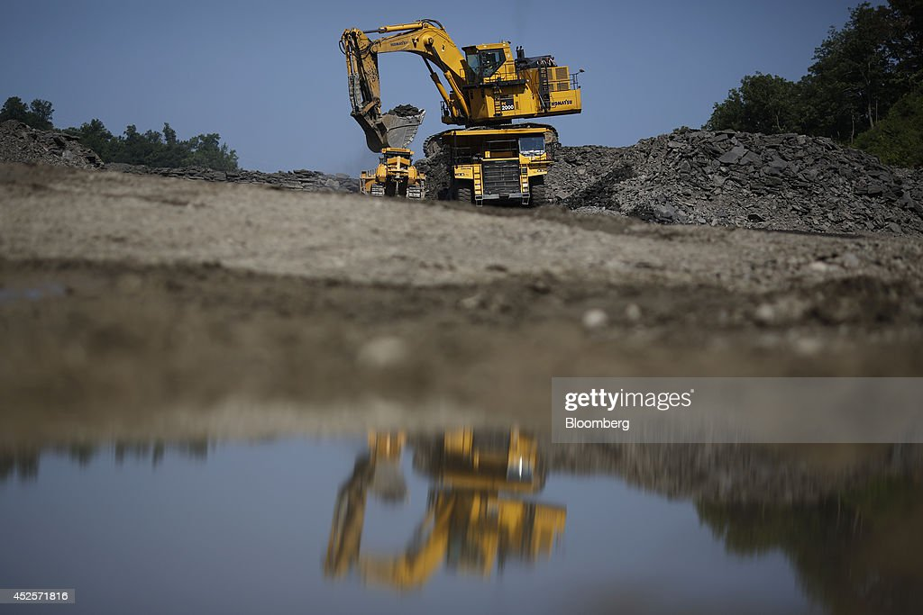 An excavator distributes loads of blasted rock into dump trucks during the construction of a new segment of U.S. Highway 460, part of the Appalachian Development Highway System, near the Virginia border in Elkhorn City, Kentucky, U.S. on Tuesday, July 22, 2014. Senate Democrats may bring to the floor a House-passed measure that would replenish federal funds for highway and mass-transit projects through May 2015. As part of that debate, senators could vote on two Democratic alternatives, although leaders say the House measure is more likely to prevail. Photographer: Luke Sharrett/Bloomberg via Getty Images