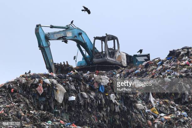 An excavator is seen on top of a garbage mountain after being set on fire by agitated survivers in Meethotamulla Colombo Sri Lanka A large section of...