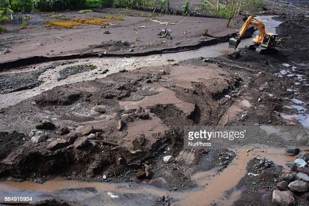 An excavator is used for transporting the sand and large rocks in the Yeh Sah River where the cold lava flows from the eruption of the Agung Mountain...