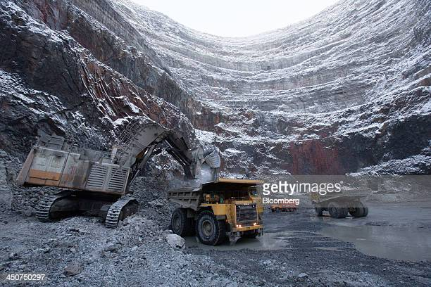 An excavator loads a dump truck with diamond ore at the base of the open pit at the Udachny diamond mine operated by OAO Alrosa in Udachny Russia on...