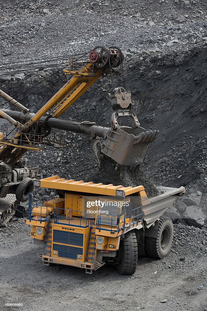 An excavator loads a transport truck with rock from the open pit of the Lebedinsky GOK (LGOK) iron ore mining and processing plant, operated by Metalloinvest Holding Co., in Gubkin, Russia, on Tuesday, May 28, 2013. Lebedinsky, Russia's third biggest iron ore mine, is owned 81 percent owned by Russian billionaire Alisher Usmanov, who also owns Mikhailovsky GOK, Russia's second-biggest iron ore mine, and Oskol Electrometallurgical Combine, a steel plant supplied by Lebedinsky. Photographer: Andrey Rudakov/Bloomberg via Getty Images